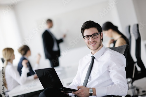 Hhandsome young business man with colleagues in background