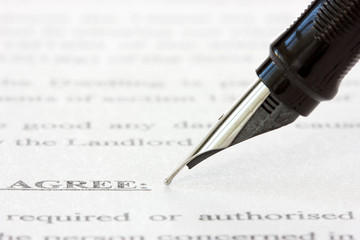 ink pen over a printed agreement