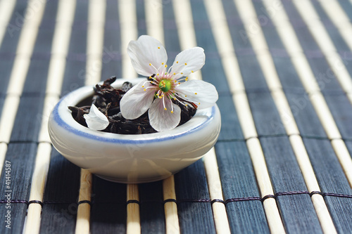 Jar of tea leaves and cherry blossoms on bamboo table cloth