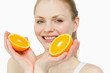 Close up of a cheerful woman holding oranges