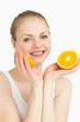 Cheerful woman holding oranges while smiling