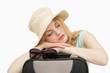 Woman asleep while leaning on a suitcase