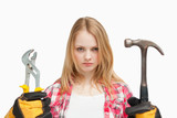 Serious woman holding a hammer and and a wrench
