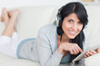 Smiling woman with headphones on while holding a tablet