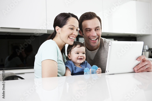 A couple and their baby son looking at a digital tablet