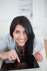 Woman smiling while touching a tactile tablet screen and holding