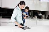 A mother and her baby son looking at a digital tablet