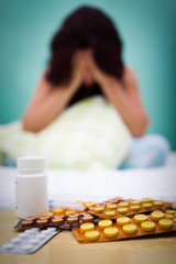Pills and out of focus sick or depressed woman