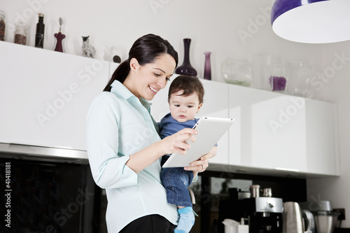 A mother with her baby son, looking at a digital tablet