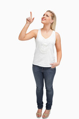 Joyful blonde woman pointing her finger up