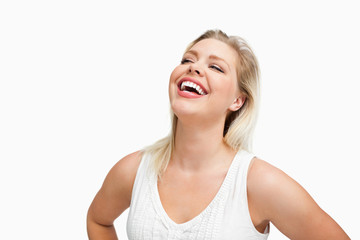 Happy woman laughing with her hands on her hips