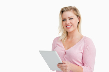 Cheerful blonde woman holding her touchscreen