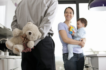 A man returning home to his family, holding a teddy bear