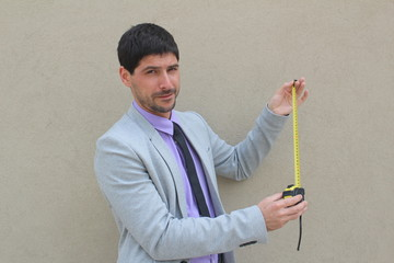 A businessman with a measuring tape