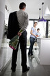 A man returning home to his family, holding a bunch of roses