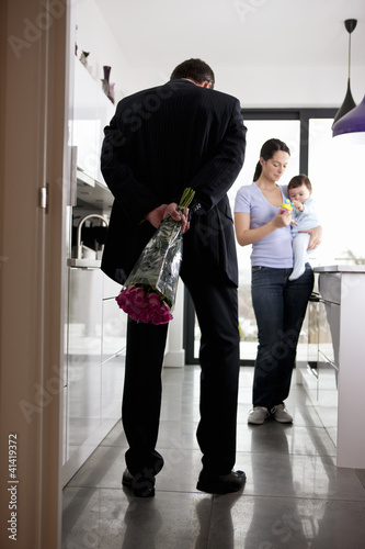 A man returning home after work, holding a bunch of roses