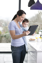 A mother and baby son looking at a digital tablet