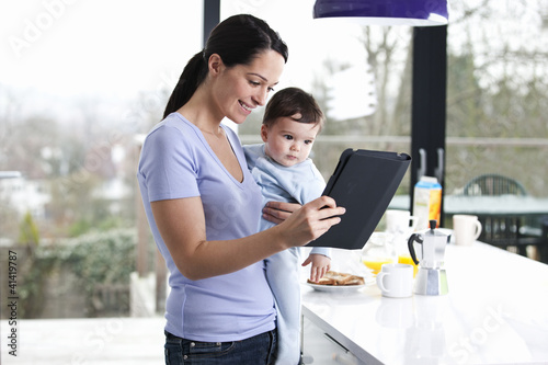 A mother holding her baby son and looking at a digital tablet