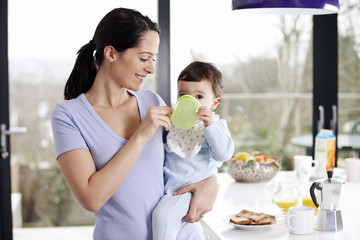 A mother standing in a kitchen giving her baby son a drink