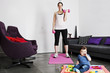 A young mother exercising at home with her baby