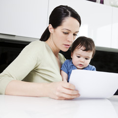 A mother and her baby son looking at paperwork