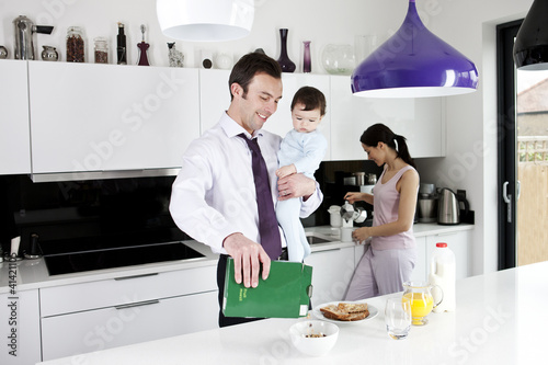 A father holding his baby son whilst making breakfast