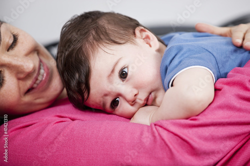 A mother cuddling her baby son on a sofa, close up