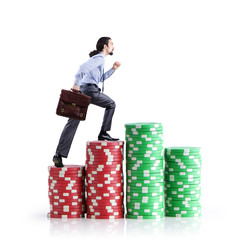 Stacks of casino chips and climbing businessman