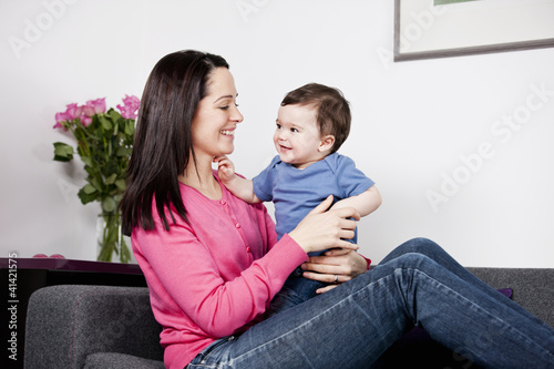 A mother sitting on a sofa holding her baby son