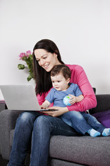 A mother and baby sitting on a sofa looking at a laptop