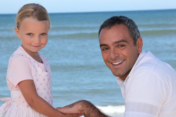 Father and daughter holding hands on the beach