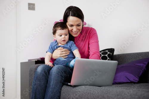 A mother and her baby son sitting on a sofa looking at a laptop