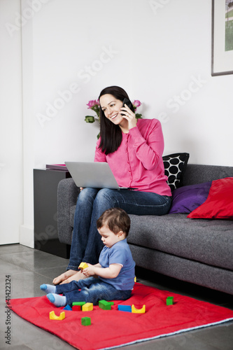 A mother using a laptop and talking on the phone, baby playing