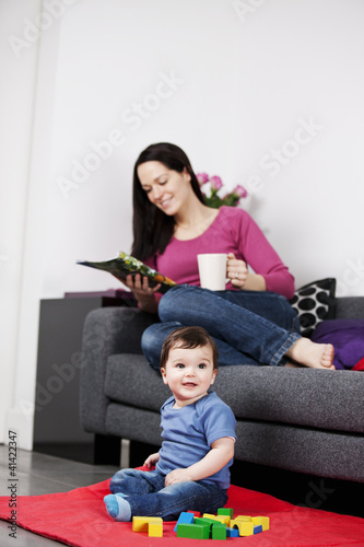 A mother relaxing on a sofa with a magazine, baby playing