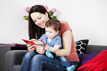 A mother and her baby son sitting on the sofa reading a book