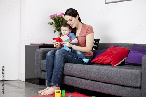 A mother and her baby son sitting on the sofa, reading a book