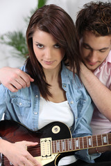 Couple sat with electric guitar
