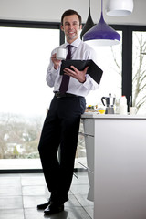 A businessman standing in a kitchen holding a digital tablet