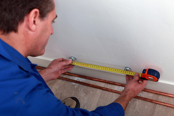Plumber measuring length of copper pipe