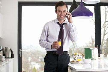 A businessman standing in a kitchen talking on a phone