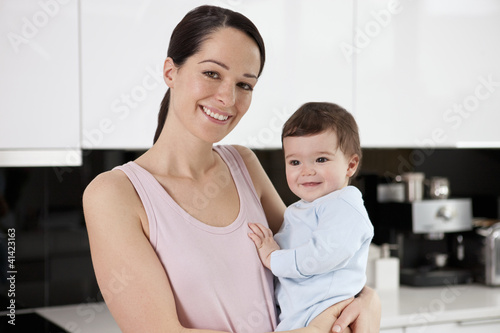 A young mother standing in a kitchen holding her baby son