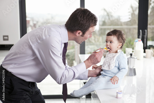 A father feeding his baby son breakfast