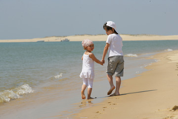 Cute boy and girl walking on the beach