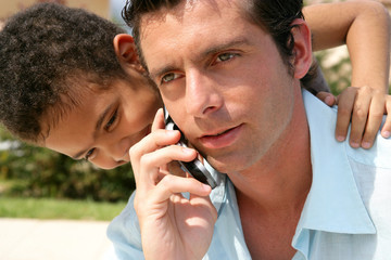 boy embracing his father while he is talking on his cell