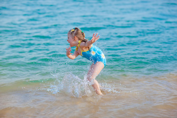 happy  girl in the sea. Fun with water drops