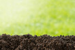 Pile of soil against green defocused background with copy space