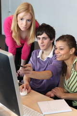 Three young people looking at a computer