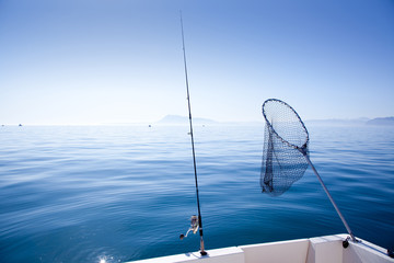 boat fishing rod and landing net in sea