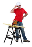 Carpenter stood with plank of wood on workbench