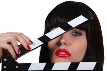Attractive woman with a film set clapboard